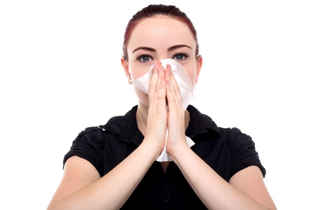 hanky: Attractive young businesswoman blowing her nose on her handkerchief after contracting seasonal flu, isolated on white