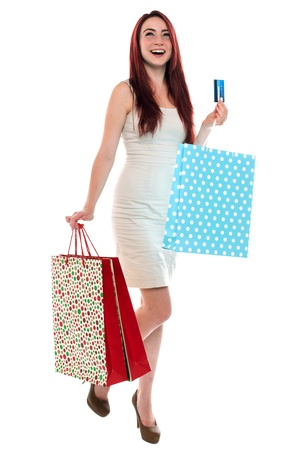 Happy excited young red haired woman carying shopping bags and holding a credit card, on white background photo