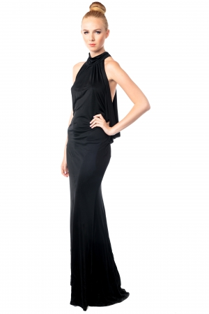 Beautiful elegant fashion model posing in a long black stylish evening gown with her hand on her hip and a serious expression, isolated on white