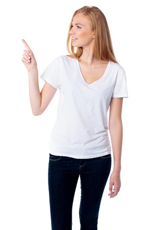 endorsing: Beautiful young blond woman standing pointing and turning to look at blank copyspace, three quarter pose on white