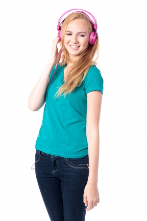 downcast: Young woman relaxing with her music standing with downcast eyes and a smile listening to her headphones, isolated on white