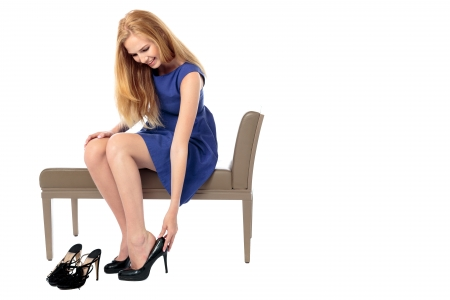 Elegant smiling young woman sitting on a bench changing her shoes for a stylish classical high heeled court shoe, isolated on white