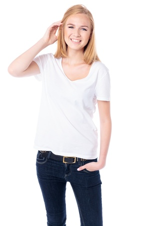 non verbal: Happy young blond female student in casual jeans standing facing the camera with her hand raised to her hair smiling at the camera, threequarter body on white