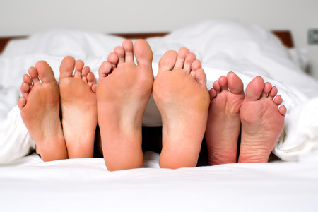 Humorous image of the bare feet of a man and two women in bed sticking out from under the bedclothes