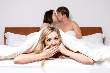 affairs: Cheeky young woman in a threesome or the cheating partner in an affair peeking out of the bottom of the bedclothes with a saucy expression as a young couple at the top of the bed share a loving kiss