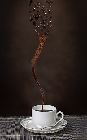 robusta: Cup of espresso with a whirlwind of coffee beans becoming a stream of ground coffee powder before finally evolving into a cup of hot freshly brewed full roast espresso in a conceptual image