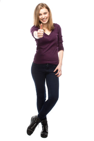 close fitting: Enthusiastic trendy modern young woman giving a thumbs up of approval and success as she poses in close fitting slacks standing smiling at the camera, isolated on white