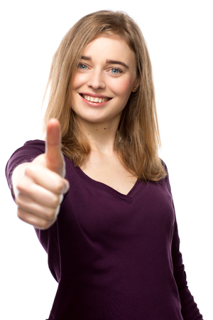 Motivated young woman giving a thumbs up gesture of success and approval with an enthusiastic smile, upper body isolated on white Foto de archivo