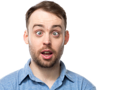 Attractive young bearded man with a comic expression of startled surprise squinting down his nose with his mouth open, isolated on white with copyspace