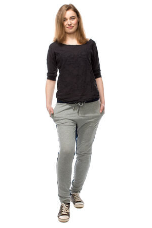 facing to camera: Beautiful confident friendly young woman posing in a relaxed position with her hands in the pockets of her casual grey slacks, full length facing the camera on white Stock Photo