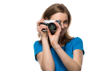 memorable: Smiling young woman photographer focusing her image as she takes a souvenir of her trip or a memorable event, isolated on white Stock Photo
