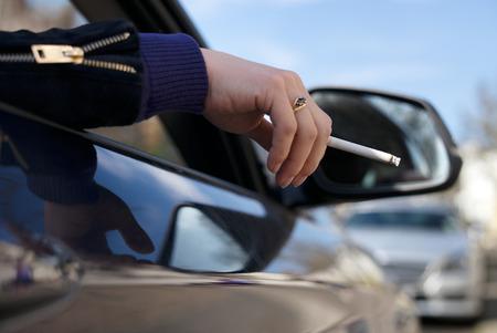 Woman holding a ciggarette outside of car window