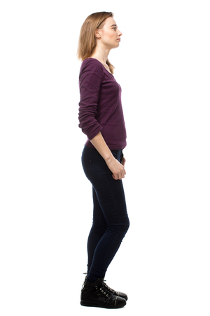 woman profile: Thoughtful slender young woman in casual clothes standing sideways staring off into the distance with a pensive expression, full length isolated on white