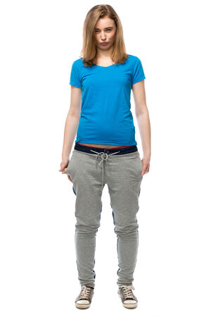 sulky: Sulky beautiful young woman in track pants and sneakers standing pouting at the camera with a frown and her hands in her pockets, isolated on white