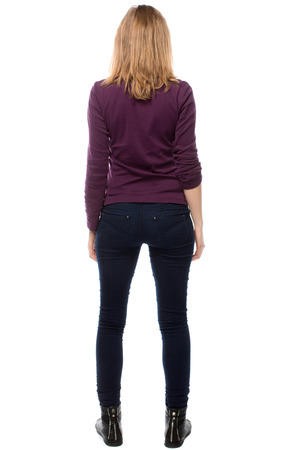 close fitting: Rear view of a trendy slender modern young woman in close fitting pants standing with her legs apart, isolated on white Stock Photo