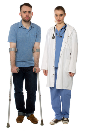 Man on Crutches and Lady Doctor Standing with serious faces. photo
