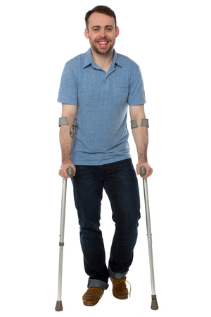recuperating: Smiling young man using crutches keeping a positive attitude in spite of his injury or handicap, full length on white Stock Photo