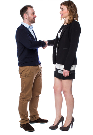Hombre joven y una atractiva mujer alta, vestida de ropa casual, de pie cara a cara, mientras sonriendo y estrechando la mano