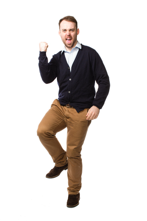 vindictive: Angry young man shaking his fist and stamping while yelling his frustration, full length isolated on white