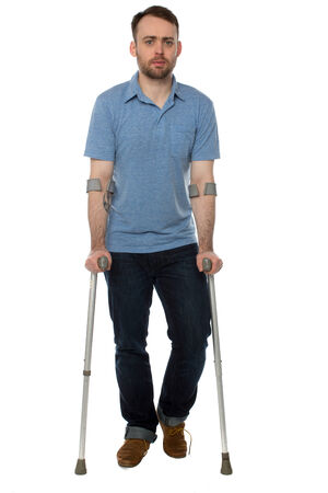 recuperating: Young disabled man wearing casual clothes while walking with forearm crutches during recovery, full length, on white Stock Photo