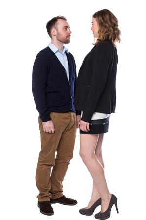 Mujer alta enfrentarse a un hombre más pisar hasta él y se eleva sobre él de una manera dominante, aislado en blanco