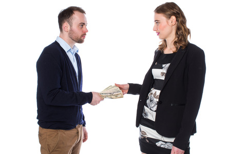 Businessman wearing dark blue sweater handing money to woman on white background.