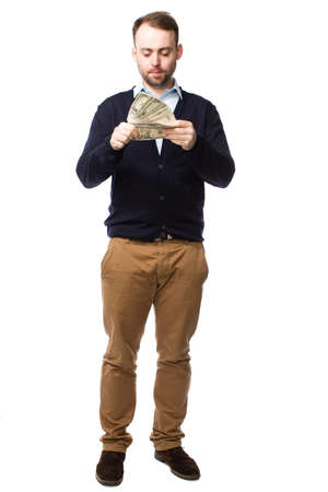 contemplates: Young man eyeing up a handful of money with a serious thoughtful expression as he contemplates making payment, full length portrait isolated on white