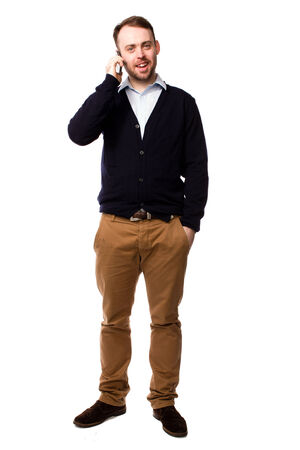 talkative: Confident young man chatting on his mobile standing facing the camera with his hand in his pocket, full length isolated on white Stock Photo