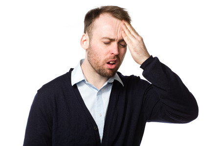 throbbing: Man rubbing his throbbing forehead with his hand as he grimaces and cries out in pain from his headache or migraine, upper body on white