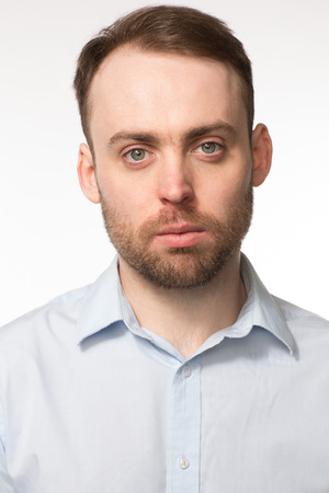 apathetic: Close-up portrait of a young handsome bearded Caucasian man, with blue eyes and light grey shirt, with a serious facial expression, on grey