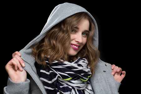 flirtatious: Happy flirtatious woman in a hooded jacket smiling as she twirls the collar in her hands on a dark background Stock Photo