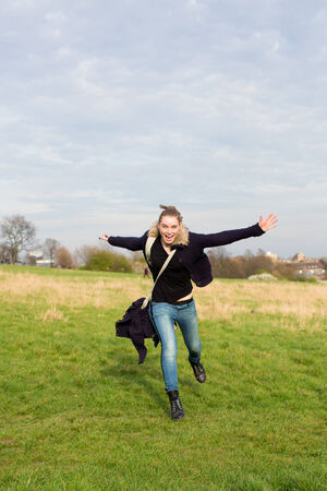 outspread: Exuberant young woman running across a field towards the camera with a handbag over her shoulder and her arms outspread Stock Photo