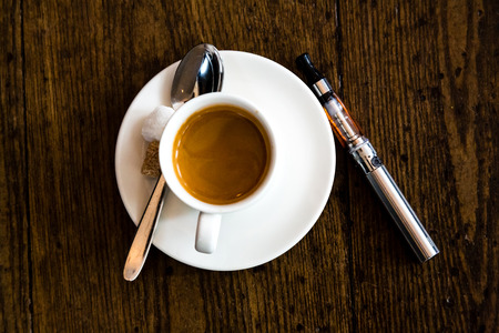 glycol: E-cigarette with a cup and saucer of milky coffee on a wooden table, view from above