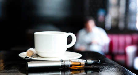 glycol: E-cigarette lying on a bar counter with a cup of aromatic coffee with a blurred man in the distance sitting drinking Stock Photo