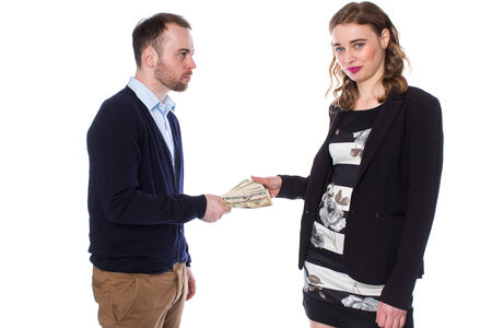 pays: Man with serious facial expression giving money to woman wearing blazer and black and white dress Stock Photo