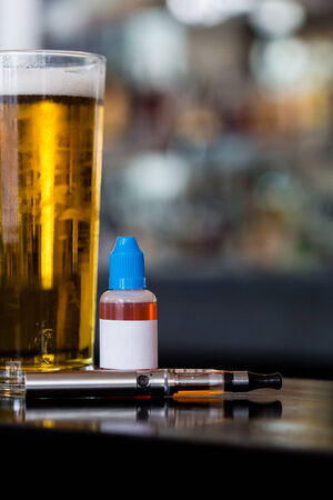 glycol: Beer, e-juice and personal vaporizer on the bar with blurry background