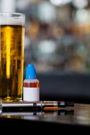 glycol: Glass of beer, e-liquid and e-cig on a table in a bar