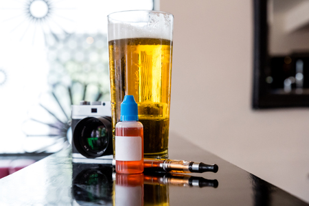 glycol: E-cigarette and refill bottle with a blank label standing on a counter with a glass of beer and digital camera in a bar, low angle with reflections and copyspace