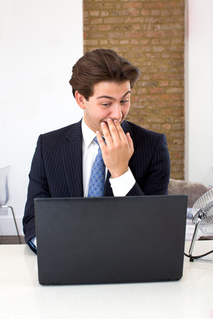 politely: Businessman reading his laptop with a snigger politely hiding his amusement behind his hand as he tries not to laugh Stock Photo
