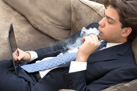 puffing: Businessman relaxing on a sofa smoking and working puffing on an electronic cigarette or e-cigarette as he reads his tablet computer