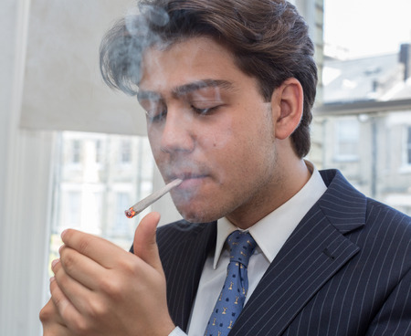 puffing: Young businessman lighting up a cigarette with a lighter in his cupped hands puffing smoke while standing in an urban office with windows