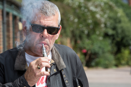 puffing: Middle-aged man in sunglasses puffing on an e-cigarette as he stands outdoors in the forecourt of a building with trees behind him and copyspace