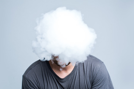 Gezicht bedekt met dikke witte rook geïsoleerd op licht Stockfoto