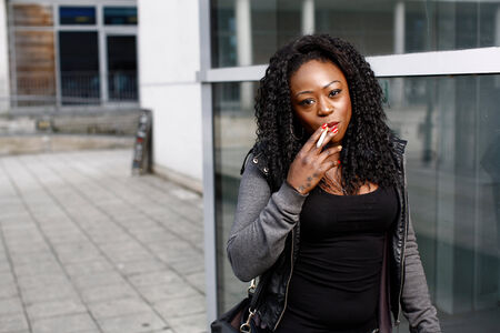 Attractive young African-American woman smoking and smiling at the camera as she walks along an urban street, with copyspace behind her 스톡 콘텐츠