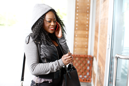 hooded top: Young African woman wearing a hooded top talking on a mobile phone as she approaches the door to an urban building Stock Photo