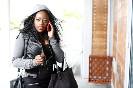 sidewalk talk: Attractive young Afro-American woman in a hooded top standing outside an urban building talking on her smartphone and looking thoughtfully off to the side