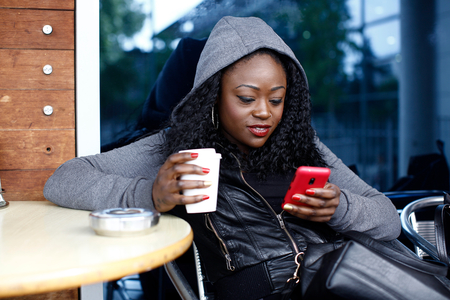 mujer sola: Mujer Joven Negro en chaqueta gris con capucha sienta en la silla que come caf� mientras Texting ocupado. Foto de archivo