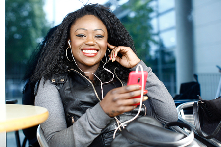 vivacious: Vivacious African woman listening to music on her MP3 player as she sits at an outdoor table at an open-air cafeteria