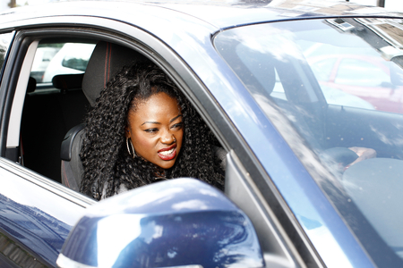 encounters: Young attractive African woman driving her car grimacing as she encounters a hold up in the traffic, viewed through the open side window
