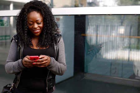 Young African woman sending an sms on her mobile smiling as she types in the text with her thumbs on the touch screen in front of an urban building photo